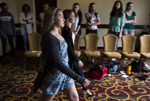 Madisyn Martinelli, 12, of New Milford, Conn., and Heather Duenas, 14, of Stafford, Va., practice their runway walk at a modeling camp at the Courtyard Marriott Hotel in McLean, Va., on Tuesday, August 18th, 2015. (Photo by Brittany Greeson/The Washington Post)