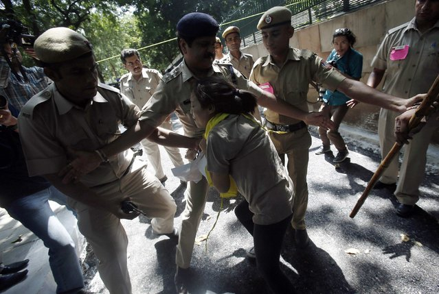 A Tibetan exile scuffles with police during a protest outside the venue of a meeting between China's President Xi Jinping and Indian Prime Minister Narendra Modi in New Delhi September 18, 2014. Groups of Tibetan activists held noisy protests outside the hotel where Xi was staying in New Delhi, and at the stately Hyderabad House where he sat down for formal talks with Modi. (Photo by Adnan Abidi/Reuters)