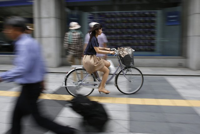 A woman cycles in front of a brokerage in Tokyo September 25, 2014. Japan's Nikkei share average rose to a fresh seven-year high on Thursday as strong U.S. economic data and continuing yen weakness buoyed investors' risk appetite, with buying extending beyond exporters to lift all sectors. (Photo by Toru Hanai/Reuters)