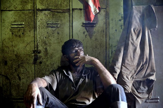 In this Tuesday, August 19, 2014 photo, an Iranian coal miner smokes a cigarette during a break at a mine on a mountain in Mazandaran province, near the city of Zirab 212 kilometers (132 miles) northeast of the capital Tehran, Iran. (Photo by Ebrahim Noroozi/AP Photo)
