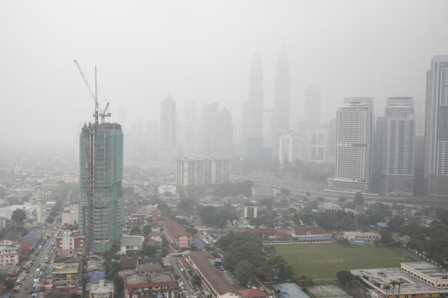 Malaysia's landmark building Petronas Twin Towers, center, and other buildings are shrouded by haze in Kuala Lumpur, Malaysia on Tuesday, September 15, 2015. A layer of heavy haze has forced Malaysian authorities to shut schools in four states, including Kuala Lumpur, with officials to begin cloud seeding operations to try to induce rain to help clear the air. (Photo by Joshua Paul/AP Photo)