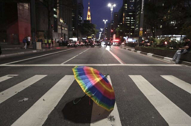 A rainbow coloured umbrella is seen on a zebra crossing in front of military police during a protest against remarks by Brazilian presidential candidate Levy Fidelix against homosexuality during televised debates, in Sao Paulo September 30, 2014. Brazil will be be holding its general elections on October 5, to elect the country's National Congress, president, state governors and state legislatures. (Photo by Nacho Doce/Reuters)