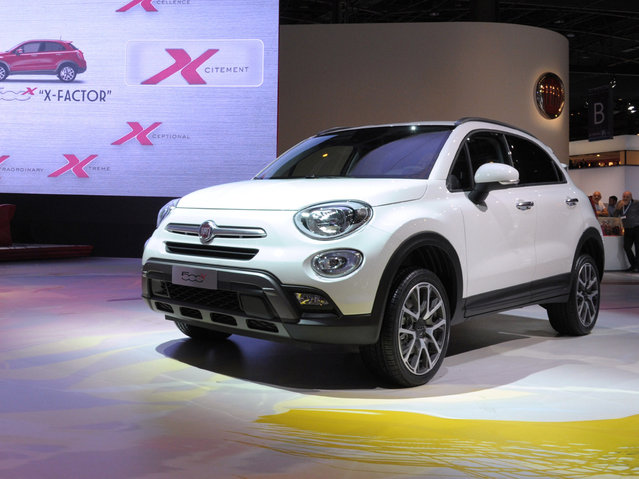 The Fiat 500 X is unveiled at the Paris Auto Show in front of the Fiat 500 wooden prototype on October 2, 2014 on the first of the two press days. (Photo by Eric Piermont/AFP Photo)