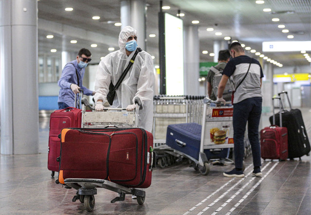 People who have arrived from New York City on an Aeroflot – Russian Airlines flight, carry their luggage at the arrivals area of Sheremetyevo International Airport in Moscow Region, Russia on June 17, 2020. (Photo by Sergei Bobylev/TASS via Getty Images)