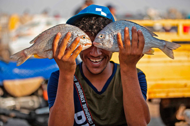 A youth poses while holding two fishes before his face in Iraq's southern port city of al-Faw, 90 kilometres south of Basra near the Shatt al-Arab and the Gulf, on May 18, 2020. In Iraq, a national lockdown to halt the COVID-19 coronavirus pandemic has found some unexpected fans: local businesses who no longer have to compete with Turkish, Iranian or Chinese imports. Those countries, as well as Saudi Arabia, Jordan and Kuwait, typically flood Iraqi markets with inexpensive products at prices local producers can't compete with. (Photo by Hussein Faleh/AFP Photo)