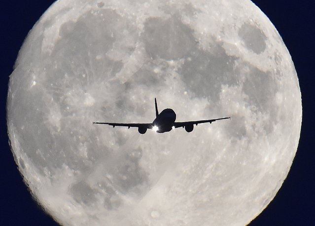 A passenger plane passes in front of the full moon as it makes a final landing approach to Heathrow Airport in west London, October 7, 2014. Heathrow Airport Holdings (HAH) is set to sell three British airports for 1 billion pounds ($1.6 billion) to a group including Spanish infrastructure firm Ferrovial, Singapore sovereign fund GIC and Australian bank Macquarie, according to Sky News. (Photo by Toby Melville/Reuters)