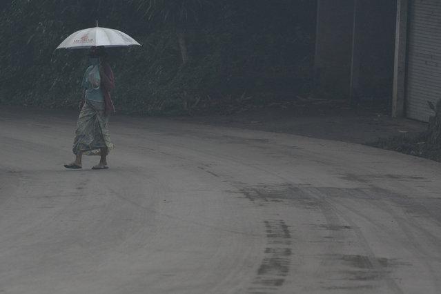 A woman uses an umbrella as she walks through ash from Mount Agung volcano during an eruptiuon in Bebandem Village, Karangasem, Bali, Indonesia on November 26, 2017. (Photo by Fikri Yusuf/Reuters/Antara Foto)