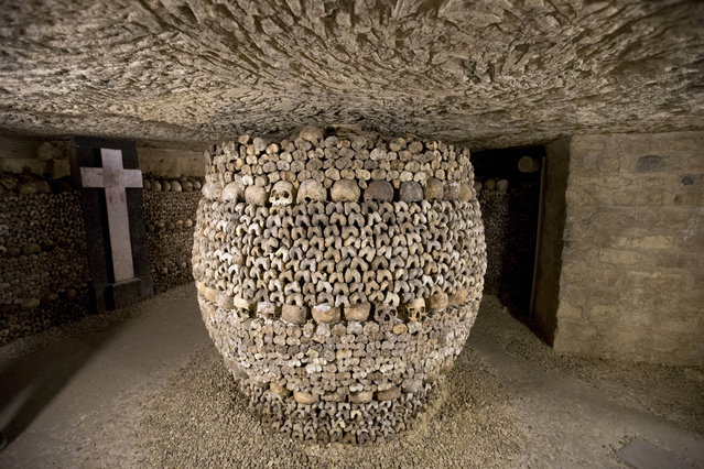 In this photo taken Tuesday, October 14, 2014, skulls and bones are stacked at the Catacombs in Paris, France. (Photo by Francois Mori/AP Photo)