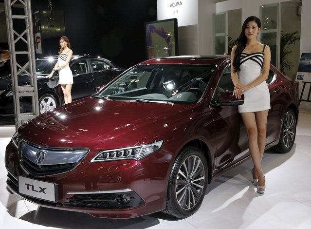 A promotional model poses next to an Acura TLX car during the Imported Auto Expo in Beijing, China, September 24, 2015. (Photo by Kim Kyung-Hoon/Reuters)