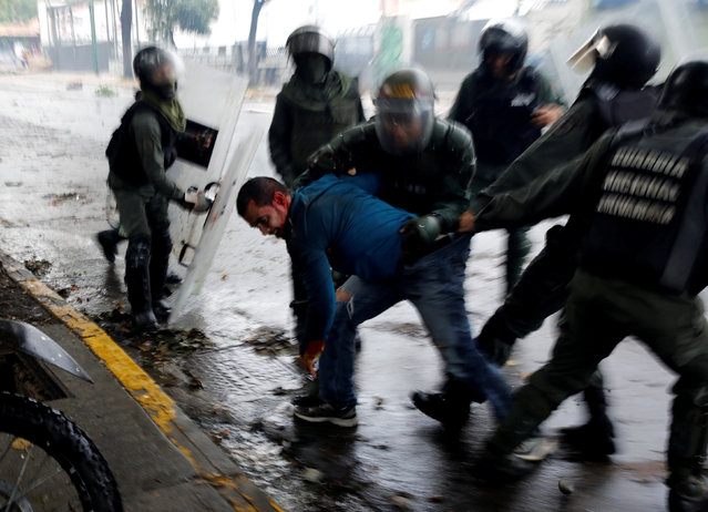 """Riot security forces detain a demonstrator during a rally against Venezuela's President Nicolas Maduro's government in Caracas, Venezuela, July 28, 2017. Rock-throwing Venezuelans braved tear gas and rainstorms, blocking streets in protest against a legislative super-body to be elected two days later that critics call an attempt by President Nicolas Maduro to create a dictatorship. Carlos Garcia Rawlins: """"After many hours of very violent clashes between the demonstrators and security forces, the National Guard in an attempt to end the situation, suddenly advanced their line very quickly, even going beyond where I and other photographers were taking cover. All the protesters who did not react fast enough to leave the place were detained"""". (Photo by Carlos Garcia Rawlins/Reuters)"""