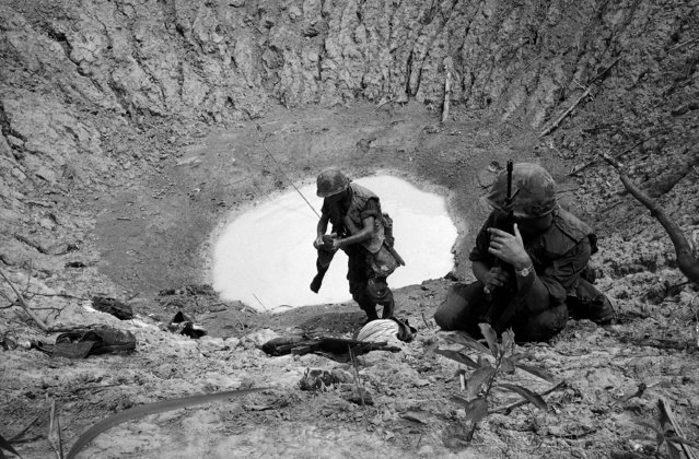 Soldiers of the 25th Infantry Division take shelter in crater caused by bomb from a B52  in the Ho Bo Woods, some 25 miles northwest of Saigon in South Vietnam on September 29, 1967. The division, supported by strikes from the B52 bombers, has been clearing 18,000 acres of the woods in effort to rout entrenched enemy. (Photo by Dang Van Phuoc/AP Photo)