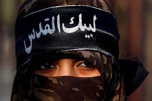 """A supporter of religious and political party Jamaat-e-Islami (JI) wears a head band that reads in Urdu, """"I am here Al Quds"""" as she attends a rally against U.S. President Donald Trump's decision to recognize Jerusalem as the capital of Israel, in Karachi, Pakistan December 17, 2017. (Photo by Akhtar Soomro/Reuters)"""