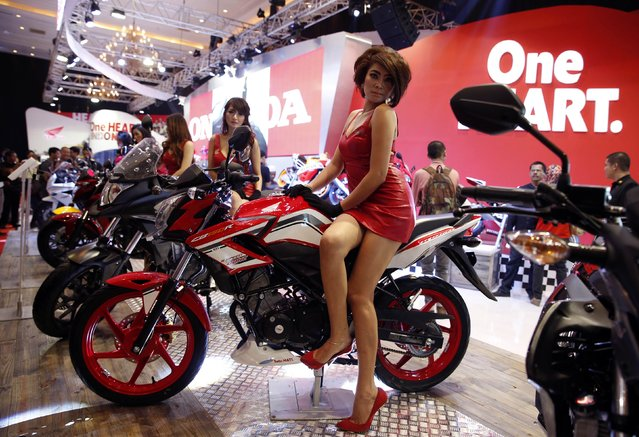 A model sits on a Honda CB150R motorcycle as she poses for photographs during the Indonesia Motorcycle Show in Jakarta October 29, 2014. (Photo by Reuters/Beawiharta)