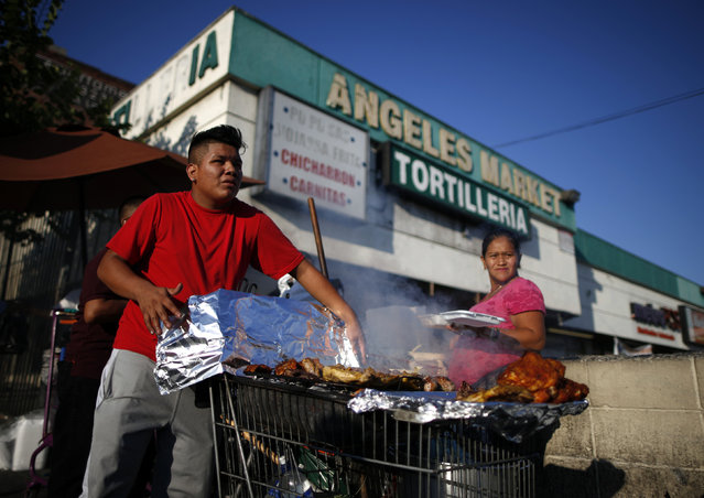 A man cooks meat in a shopping cart in the Westlake area of Los Angeles, home to many Mexican and Central American migrants, California August 6, 2014. (Photo by Lucy Nicholson/Reuters)