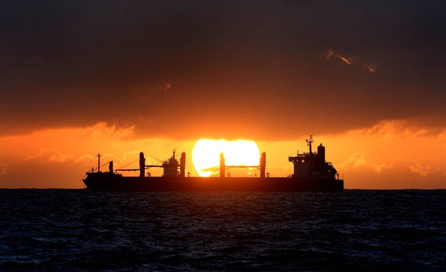The sun rises behind a ship as it enters the North Sea from the river Tyne near Tynemouth, on October 15, 2014. (Photo by Owen Humphreys/PA Wire)