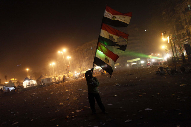 An Egyptian protester waves his national flag in Cairo's Tahrir square on January 25, 2013. Protesters stormed a regional government headquarters and clashed with police as mass rallies shook Egypt on the second anniversary of a revolt that ousted Hosni Mubarak and brought Islamists to power. (Photo by Mahmoud Khaled/AFP Photo/The Atlantic)
