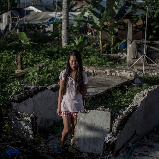 Typhoon Haiyan survivor Mariena Delacueva stands amongst the ruins of her families home on November 6, 2014 in San Antonio, Samar, Philippines. Mariena's looks after the property after her parents moved to Manila to find work so they can save enough money to rebuild the house. (Photo by Chris McGrath/Getty Images)