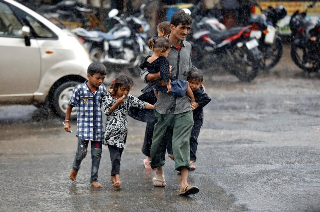 A man carrying children crosses a road during heavy rains in Ahmedabad, India, August 31, 2020.. (Photo by Amit Dave/Reuters)
