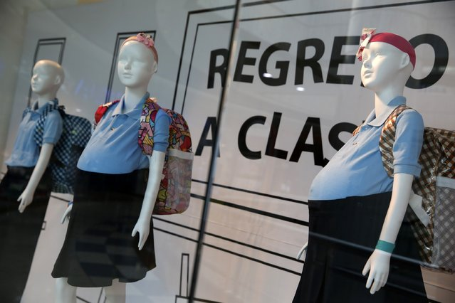 Mannequins of pregnant schoolgirls are seen in a shop window at a shopping mall in Caracas November 12, 2014. A display showing mannequins of pregnant schoolgirls at a Caracas mall is shocking shoppers and stirring debate over s*x education in Venezuela. Two local charities have dressed up three mannequins behind a shop window as girls with bulging stomachs under the blue uniforms used by schoolchildren here until age 15. (Photo by Carlos Garcia Rawlins/Reuters)