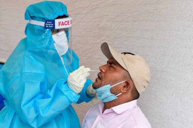 A health worker collects a swab sample from a man to test for the Covid-19 coronavirus at a roadside testing booth in Ahmedabad on September 14, 2020.  India's coronavirus cases are now the second-highest in the world and only behind the United States. (Photo by Sam Panthaky/AFP Photo)