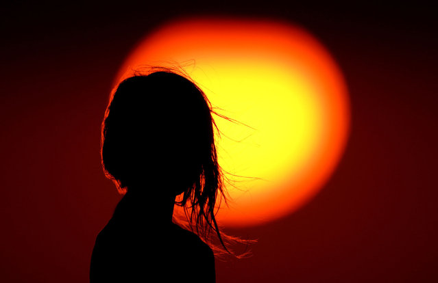A girl watches the sunset from a park in Kansas City, Mo. as a hot summer day comes to an end Wednesday, August 26, 2020. Sunsets have been a bit more colorful than normal as smoke from California wildfires drifts into the central part of the country. (Photo by Charlie Riedel/AP Photo)