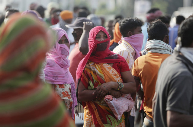 Migrant laborers from other states looking for work gather on a street on the outskirts of Jammu, India, Sunday, September 27, 2020. The nation of 1.3 billion people is expected to become the coronavirus pandemic's worst-hit country within weeks, surpassing the United States. (Photo by Channi Anand/AP Photo)