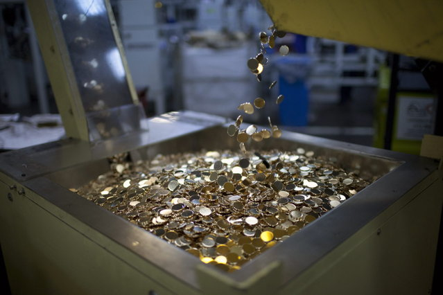 Metal discs fall into a stamping machine to make R$ 0.25 coins, or 25 centavos, at the Casa da Moeda, the national mint, in the Santa Cruz suburb of Rio de Janeiro, Brazil, on Tuesday, March 5, 2013. Brazil is likely to keep its key interest rate at a record low for the third straight meeting, as policy makers are caught between a fragile economic recovery and faster-than-expected inflation. (Photo by Dado Galdieri/Bloomberg)