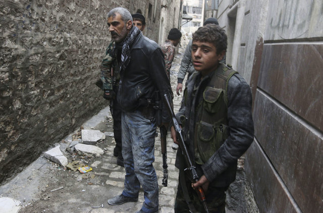 Rebel fighters carry their weapons as they stand along an alleyway at the frontline against forces loyal to Syria's President Bashar al-Assad in Maysaloun neighborhood in the old city of Aleppo November 24, 2014. (Photo by Abdalrhman Ismail/Reuters)