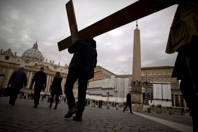 People carry a cross on their way to pray in St. Peter's Square at the Vatican, where Cardinals gathered for their final day of talks before the conclave to elect the next pope, on March 11, 2013. (Photo by Oded Balilty/Associated Press)