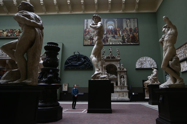An employee poses next to a five metre high cast of Michelangelo's David during a press preview for the newly renovated Weston Cast Court at the Victoria and Albert Museum on November 26, 2014 in London, England. (Photo by Carl Court/Getty Images)