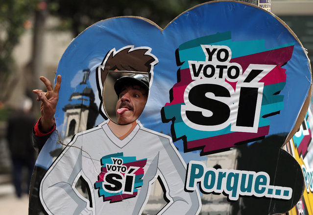 "A man poses for a photo behind a cut-out supporting the ""yes"" vote ahead of a referendum on the peace deal between the government and rebels of the Revolutionary Armed Forces of Colombia, FARC, in Bogota, Colombia, Thursday, September 29, 2016. Colombians will vote on Oct. 2 in a referendum where they will be asked to ratify or reject the deal. (Photo by Fernando Vergara/AP Photo)"