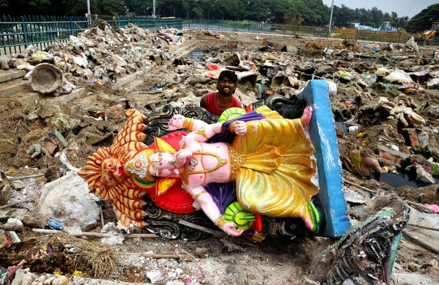 A laborer lifts an idol of elephant-headed Hindu god Ganesha as he cleans a pond filled with piles of other similar idols immersed by devotees during recently concluded Ganesha Chaturthi festival in Bangalore, India, Monday, September 26, 2016. Every year millions of devout Hindus immerse idols of god Ganesh into water bodies at the end of the festival that celebrates the birth of the Hindu god. (Photo by Aijaz Rahi/AP Photo)