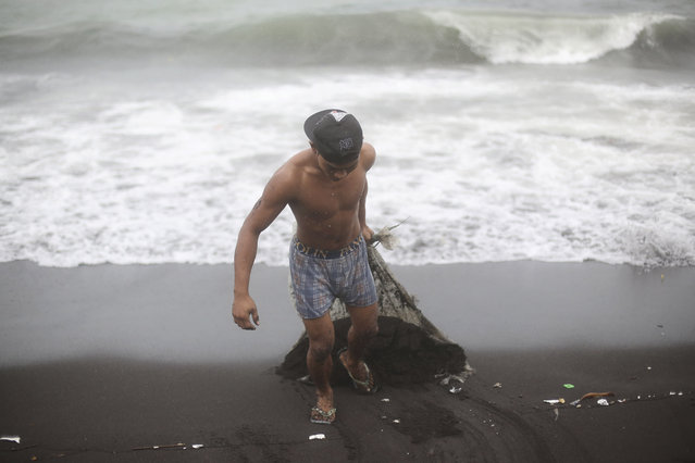 A Filipino man brings out sand which he retrieved from his house after strong waves from Typhoon Hagupit battered a coastal village in Legazpi, Albay province, eastern Philippines on Monday, December 8, 2014. (Photo by Aaron Favila/AP Photo)