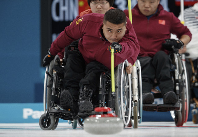 China's Wang Haitao throws the stone  during the Wheelchair Curling Round Robin Session against South Korea at the Gangneung Curling Centre in Gangneung at the Paralympic Winter Games, South Korea, Thursday, March 15, 2018. (Photo by Simon Bruty/OIS/IOC via AP Photo)