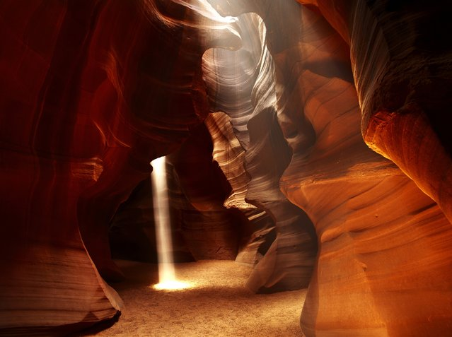 """A single shaft of sunlight illuminates airborne particles of dust. Upper Antelope Canyon in Arizona is about 40 meters (130 feet) deep and except for a couple chambers, it is extraordinarily narrow and twisted"". (Photo by Art Wolfe/Art Wolfe Stock)"
