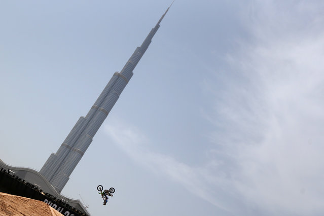 A motocross rider shows his skills during a training session outside Burj Khalifa on the eve of the 2013 Red Bull X-Fighters World Tour in the Gulf emirate of Dubai on April 11, 2013. (Photo by Marwan Naamani/AFP Photo)