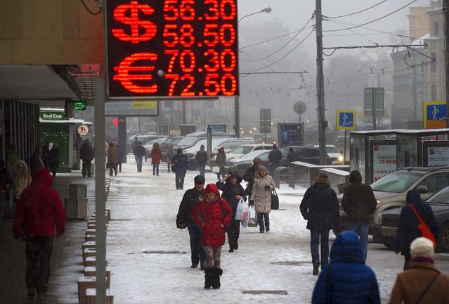 People walk past a sign advertising currency exchange rates in Moscow, Russia, Friday, December 12, 2014. The ruble hit another record low against the dollar even after Russia's Central Bank sought to ease the selling pressure on the currency by raising interest rates again. (Photo by Alexander Zemlianichenko/AP Photo)
