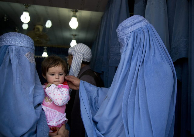 In this Thursday, April 11, 2013 photo. an Afghan woman comforts the child of her friend as both wait to get in line to try on a new burqa in a shop in the old town of Kabul, Afghanistan. (Photo by Anja Niedringhaus/AP Photo)