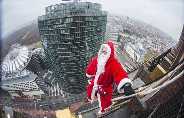 A man dressed as a Santa Claus climbs at the front of the Kollhoff Tower at Potsdamer Platz square in Berlin December 14, 2014. (Photo by Hannibal Hanschke/Reuters)