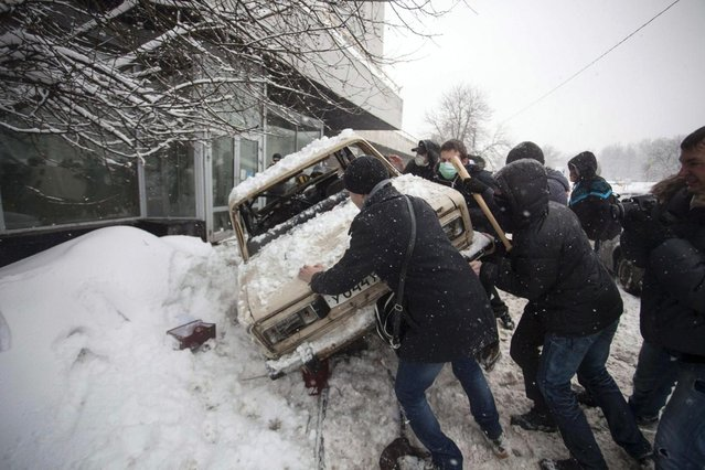 In this photo taken on Friday, March 15, 2013, members of a pro-Kremlin youth group upturn the car that belongs to pushers of spice, a synthetic drug, in Moscow, Russia. Russian officials and anti-drugs campaigners say that spice has become one of the most dangerous drugs widely available to youngsters and almost impossible to ban because of the constantly changing chemical ingredients. (Photo by Alexander Zemlianichenko Jr/AP Photo)