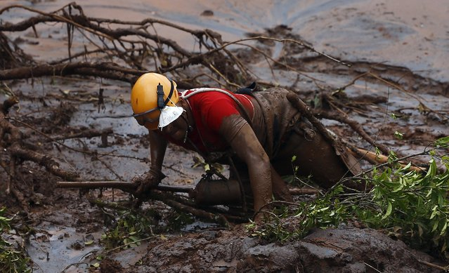 A rescue worker searches for victims at Bento Rodrigues district that was covered with mud after a dam owned by Vale SA and BHP Billiton Ltd burst, in Mariana, Brazil, November 8, 2015. Brazilian authorities on Sunday confirmed a second death caused by a massive mudflow and flooding that swamped towns near an iron ore mine in the southeastern state of Minas Gerais. (Photo by Ricardo Moraes/Reuters)