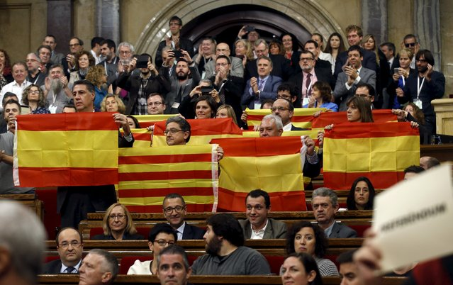 Popular Party (PP) deputies, with their leader Xavier Garcia Albiol (L), display the Spanish and Catalonian flags as Catalonia's regional government reacts after voting in favor of a resolution to split from Spain at Parlament de Catalunya in Barcelona, Spain, November 9, 2015. The declaration on secession, the first step which pro-independence parties hope will lead to the northeastern region splitting from Spain within 18 months, was backed by a majority in the regional parliament. (Photo by Albert Gea/Reuters)