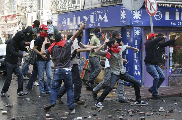 May Day protesters throw stones at riot police as they try to break through barricades to reach the city's main square in central Istanbul May 1, 2013. Turkish riot police clashed with thousands of May Day protesters in Istanbul on Wednesday, firing water cannons and tear gas at crowds that tried to break through barricades to reach the city's main square, witnesses said. The incidents followed the pattern of recent years, when May Day demonstrations in Turkey's largest city have often been marked by clashes between police and protesters. (Photo by Serkan Senturk/Reuters)