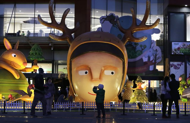 A boy takes a photo of Christmas decorations in front of a shopping mall in Beijing December 24, 2014. (Photo by Jason Lee/Reuters)