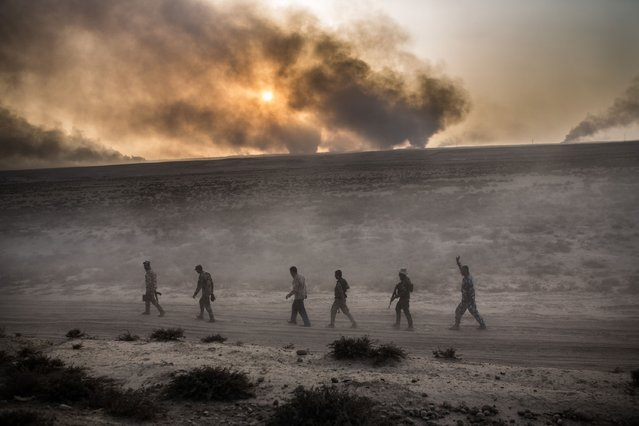 Iraqi soldiers walk on a road as smoke billows from the Qayyarah area, some 60 kilometres (35 miles) south of Mosul, on October 19, 2016, during an operation against Islamic State (IS) group jihadists to retake the main hub city. (Photo by Yasin Akgul/AFP Photo)