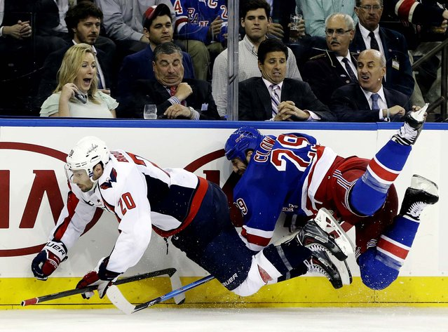 Troy Brouwer of the Washington Capitals and the Rangers' Ryane Clowe go airborne after colliding in the third period of Game 4 of their first-round Stanley Cup playoff series in New York, on May 8, 2013. The Rangers won 4-3. (Photo by Kathy Willens/Associated Press)