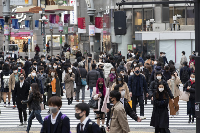 In this December 11, 2020, file photo, people wearing face masks to help curb the spread of the coronavirus walk across an intersection in Tokyo. Tokyo reported 621 new COVID-19 cases Saturday, Dec. 12, setting a new high in the capital of Japan where a lack of government measures has triggered concerns about further upsurge during the holiday season. (Photo by Hiro Komae/AP Photo/File)