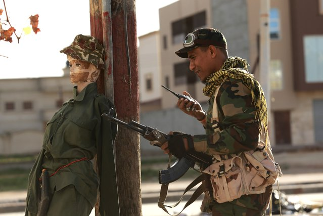 A personnel of pro-government Libyan forces, who are backed by locals, holds his weapon next to a mannequin used as a decoy against snipers during clashes in the streets with the Shura Council of Libyan Revolutionaries, an alliance of former anti-Gaddafi rebels, who have joined forces with the Islamist group Ansar al-Sharia, in Benghazi December 28, 2014. (Photo by Esam Omran Al-Fetori/Reuters)
