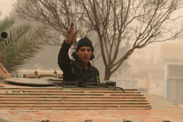 A rebel fighter reacts while riding a military vehicle in Dahiyat al-Assad, west Aleppo city, Syria October 28, 2016. (Photo by Ammar Abdullah/Reuters)