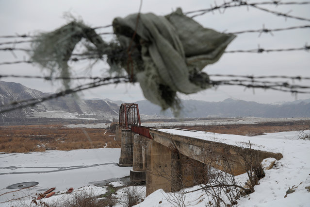 A piece of clothing is used to make a gap in barbed wire near the closed bridge over the Yalu River on the Chinese side of the border with North Korea between towns of Ji'an and Linjiang, China, November 21, 2017. A week-long road trip along China's side of its border with North Korea showed places where it is porous. (Photo by Damir Sagolj/Reuters)
